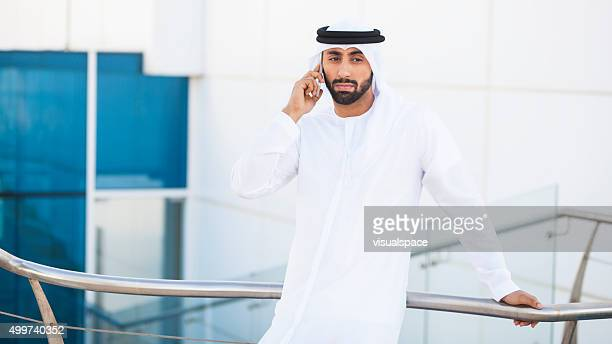 Concerned Arab Man Talking On Phone Outside Office