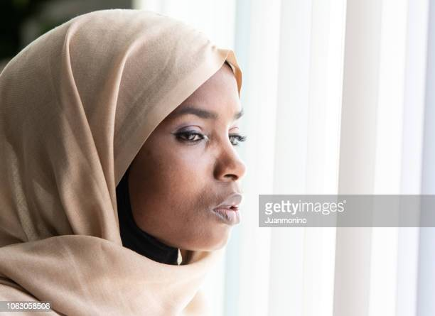 concerned black muslim woman looking through a window - prejudice stock pictures, royalty-free photos & images
