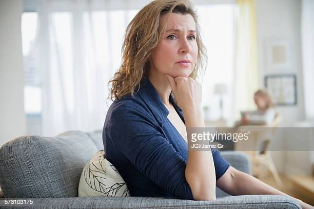 concerned caucasian woman sitting on sofa - ongerust stockfoto's en -beelden
