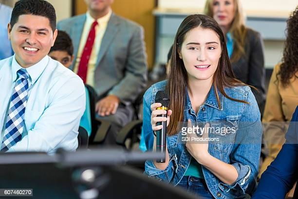 concerned citizen asks a mayoral candidate a question during meeting - town hall meeting stock photos and pictures