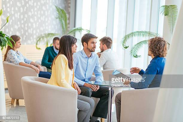 concerned couple discussing loan rates with personal banker - candid forum stock pictures, royalty-free photos & images