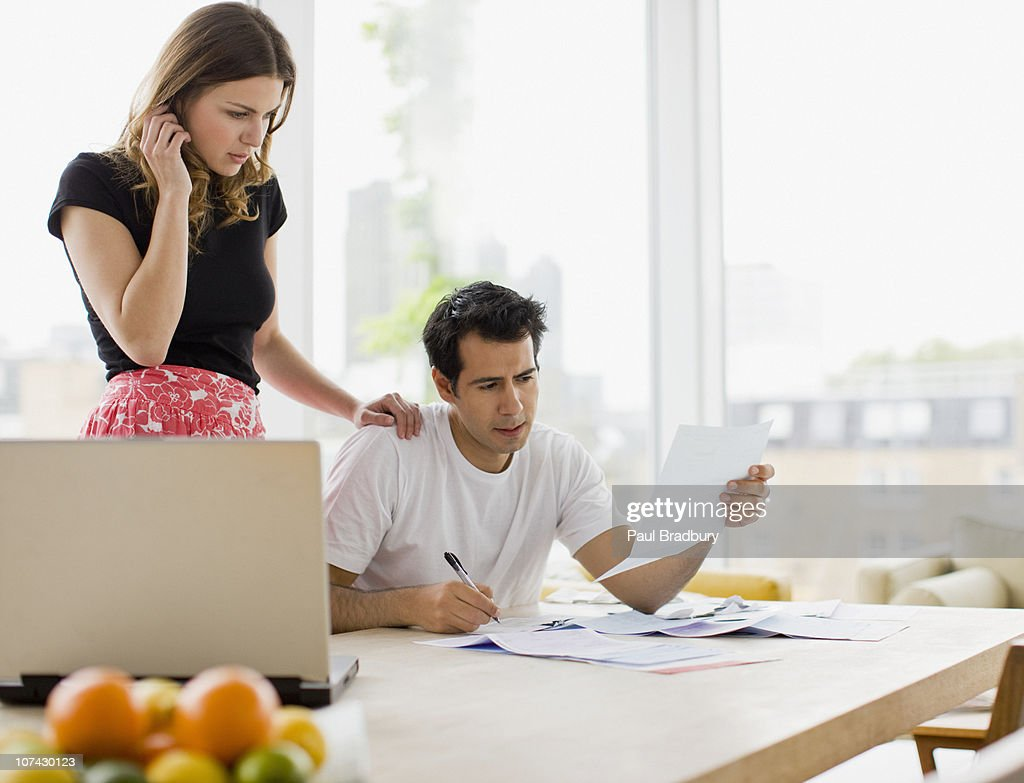 Concerned couple paying bills together : Stock Photo