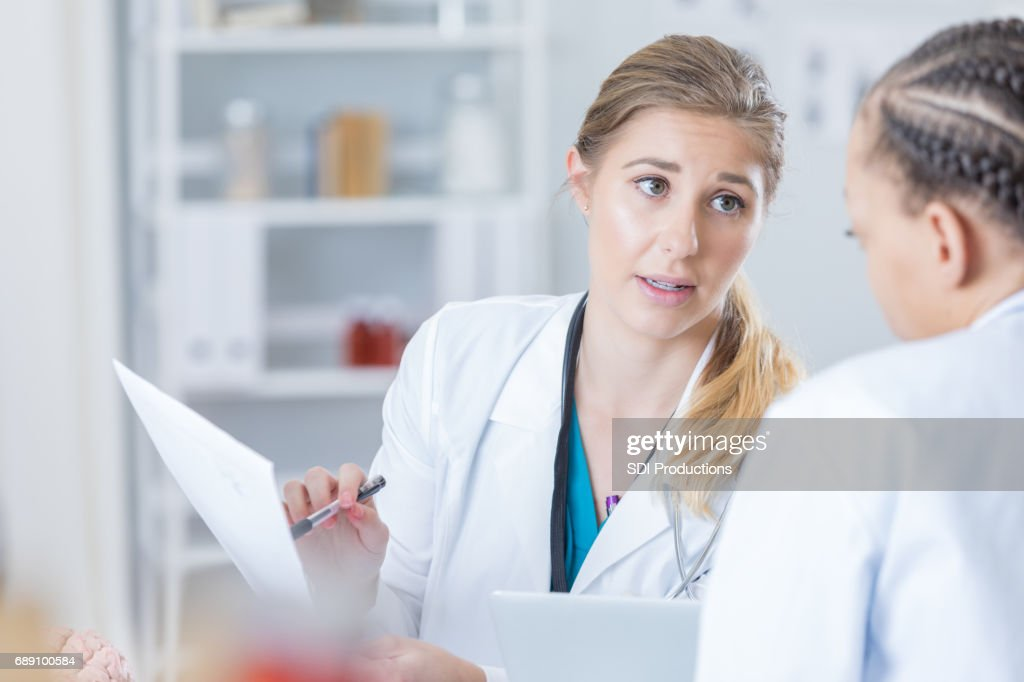 Concerned doctor discusses a patient's case with a colleague : Stock Photo