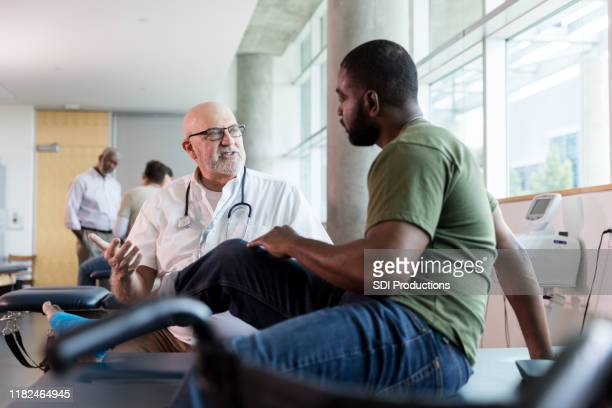 concerned doctor discusses patient's injury - army physical exam stock pictures, royalty-free photos & images