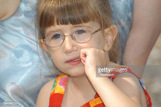 Concerned face of a little girl with disabilities, including a visual impairment.