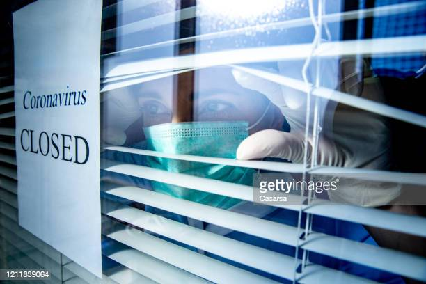 concerned healthcare worker looking through a window with a closed sign due to coronavirus - social issues stock pictures, royalty-free photos & images