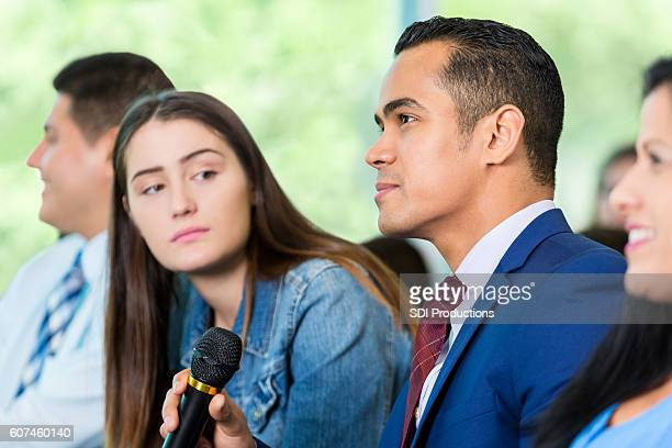 concerned hispanic man asks a question during town hall meeting - town hall meeting stock photos and pictures