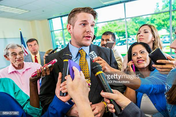 concerned man answering questions from journalists - press conference stock pictures, royalty-free photos & images
