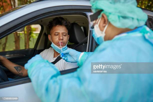 concerned man getting covid-19 nasal swab test at drive-thru - medical test stock pictures, royalty-free photos & images