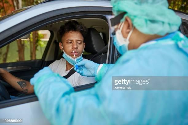 ドライブスルーでcovid-19鼻綿棒テストを受ける懸念される男 - 医療検査 ストックフォトと画像