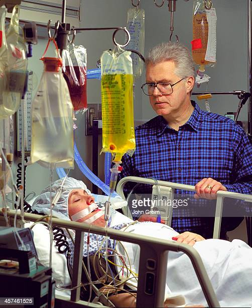 A concerned man watches over his wife in a intensive care unit