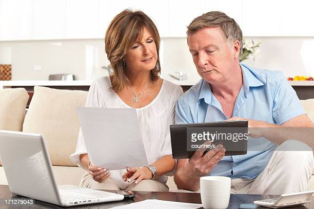 Concerned Mature couple paying bill online using a digital table