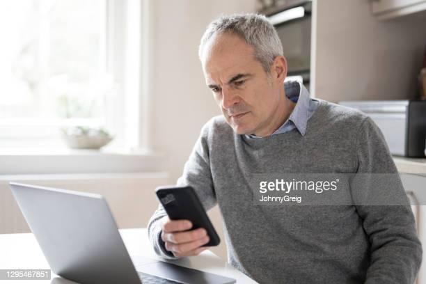 concerned mature male looking at smart phone device - candid forum stock pictures, royalty-free photos & images