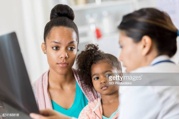 Concerned mom talks with doctor about child's x-ray