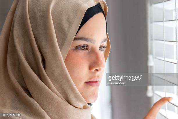 concerned muslim young woman looking through a window - veil stock photos and pictures
