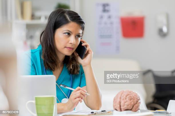 concerned neurologist uses smart phone - cerebrum stock photos and pictures