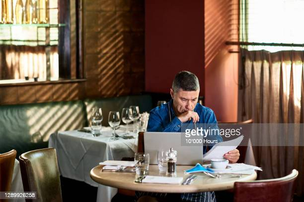 concerned restaurant owner reading document with face mask on table - finance and economy stock pictures, royalty-free photos & images