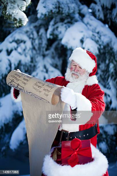 concerned santa claus reading the christmas nice/naughty list outdoors - naughty santa stock photos and pictures