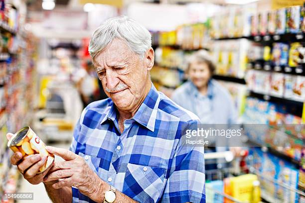 Concerned senior man checks can label in supermarket