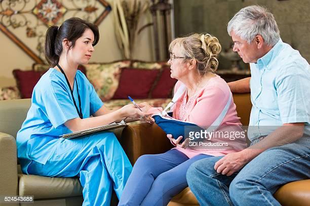 Concerned senior patient talks with home healthcare nurse