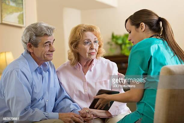 Concerned seniors with home healthcare nurse using digital tablet