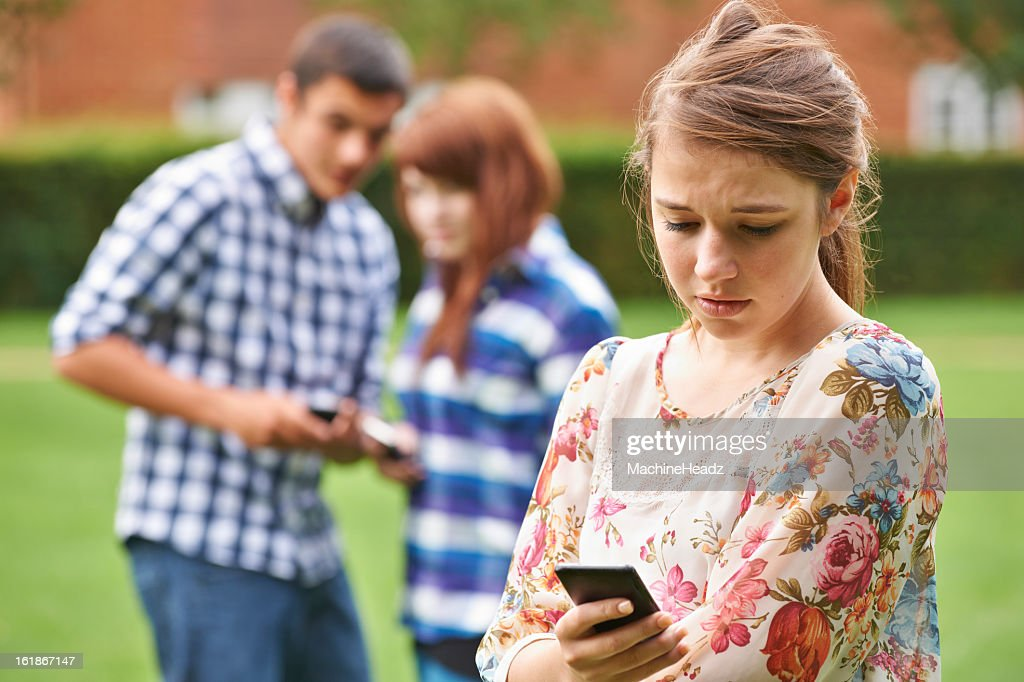 A concerned teenage girl being bullied by text message : Stock Photo