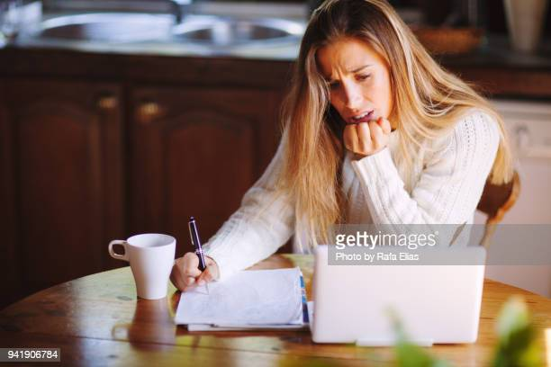 Concerned woman checking bank account in laptop