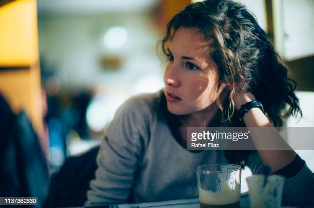 concerned woman in coffee shop - reizen stock-fotos und bilder
