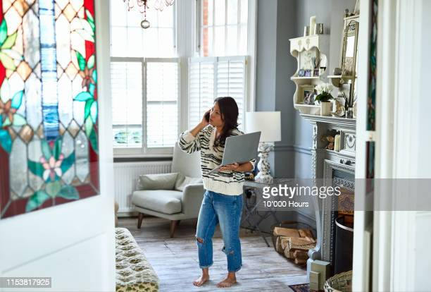 concerned woman in her 30s on phone with laptop - work from home stock pictures, royalty-free photos & images