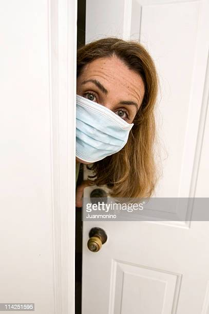 Concerned woman in surgical-mask peers out a doorway