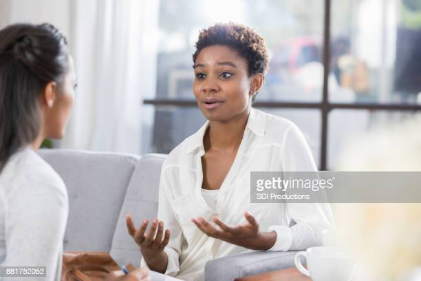 concerned woman talks with therapist - gesturing stock pictures, royalty-free photos & images