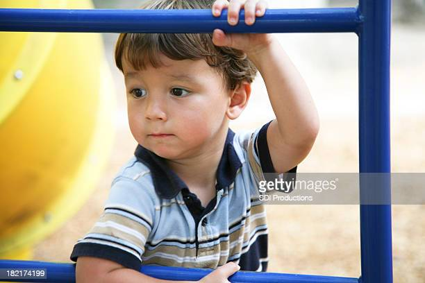 Concerned Young Boy Holding On to Bar at a Playground