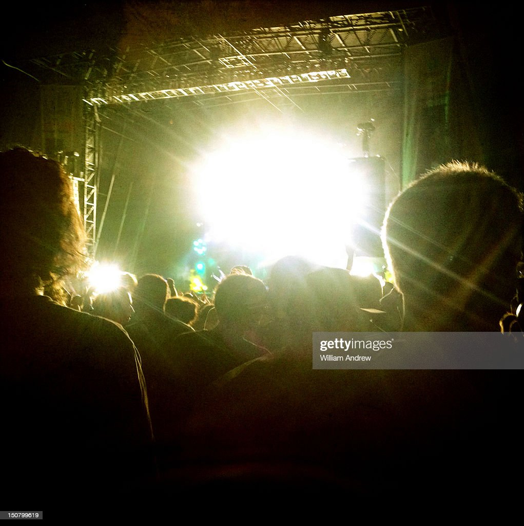 Concert crowd with glowing stage in background : Stock Photo