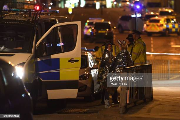 Concert goers wait to be picked up at the scene of a suspected terrorist attack during a pop concert by US star Ariana Grande in Manchester northwest...