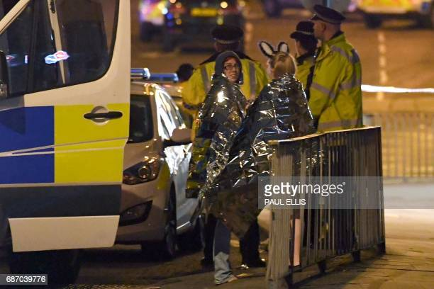 TOPSHOT Concert goers wait to be picked up at the scene of a suspected terrorist attack during a pop concert by US star Ariana Grande in Manchester...