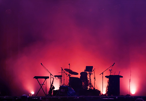 concert stage on rock festival, music instruments silhouettes 1199243596
