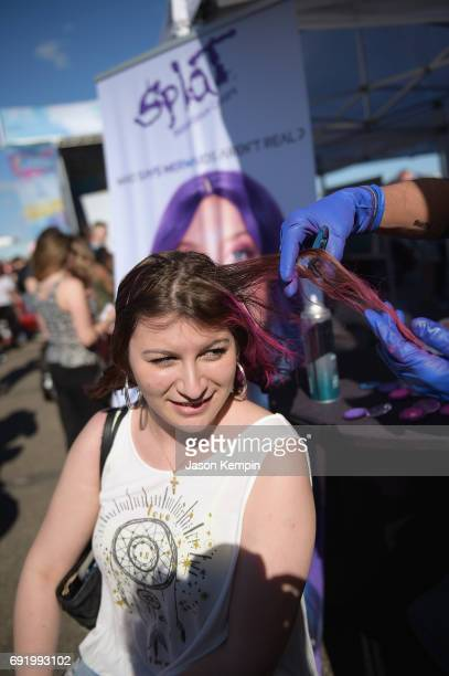 A concertgoer has her hair colored with hair chalk at the Splat Hair Color booth during 1035 KTU's KTUphoria 2017 official Pregame party at Northwell...