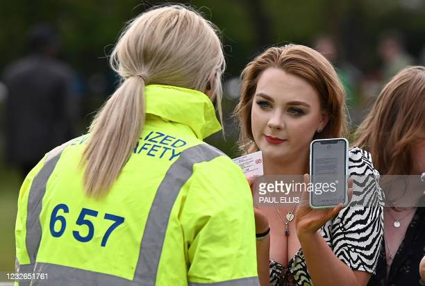 Concert-goers shows a negative Covid-19 result on their phone as well as their driving licence as they arrive at the venue for the latest event in...