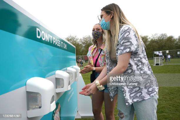Concert-goers wash their hands as they enjoy a non-socially distanced outdoor live music event at Sefton Park on May 2, 2021 in Liverpool, England....