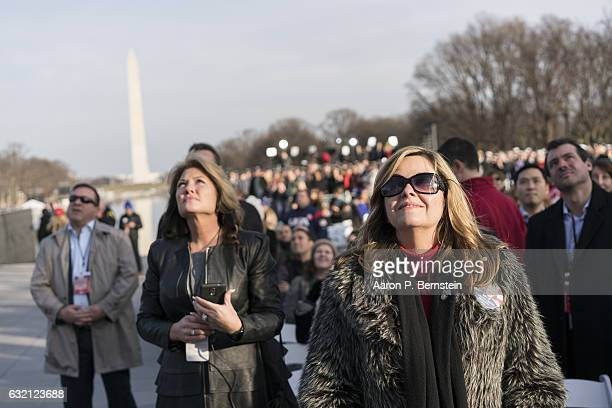 Concertgoers watch a feed of Presidentelect Donald Trump laying a wreath at Arlington Memorial Stadium during the inauguration concert at the Lincoln...