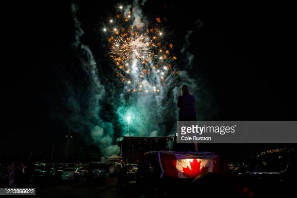 Concert-goers watch as fireworks burst behind the stage of a drive-in Dean Brody concert to celebrate Canada Day on July 1, 2020 in Markham, Canada....