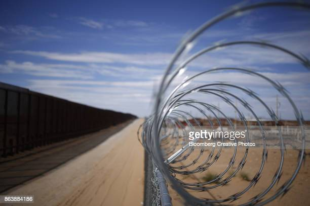 a concertina barbed wire fence stands next to a border fence that separates the u.s. and mexico - mexico border wall stock pictures, royalty-free photos & images