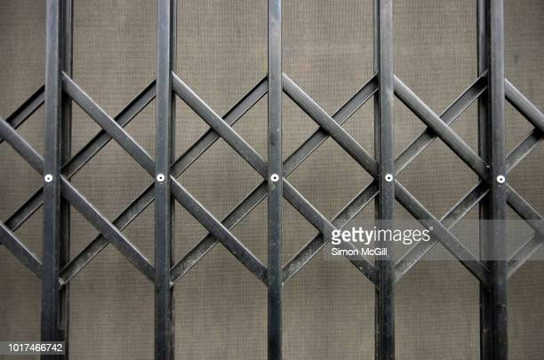 concertina metal security grille and blind across a shop window - metal grate stock pictures, royalty-free photos & images