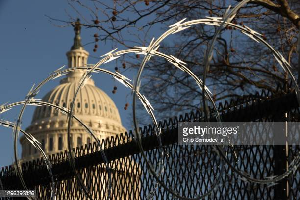 Concertina razor wire tops the 8-foot 'non-scalable' fence that surrounds the U.S. Capitol the day after the House of Representatives voted to...
