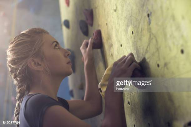 Concetrated young athlete woman hold a rock on climbing wall