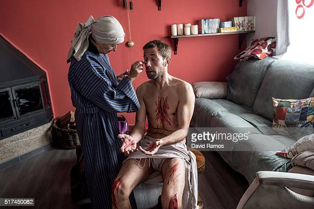 Concha makes up Felipe as he is dressing up as Jesus Christ ahead of the reenactment of Christ's suffering on March 25, 2016 in Hiendelaencina,...