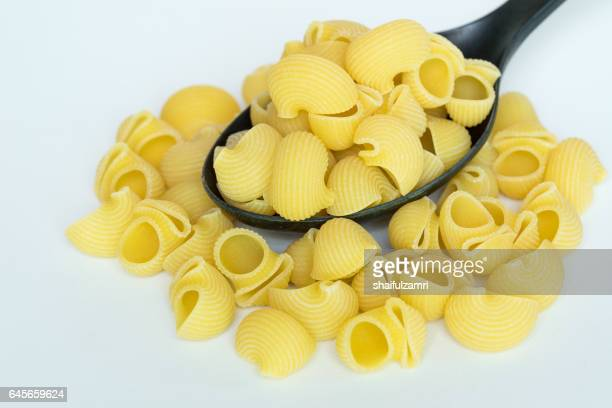 conchiglie (shells) pasta over black spatula - shaifulzamri stock pictures, royalty-free photos & images
