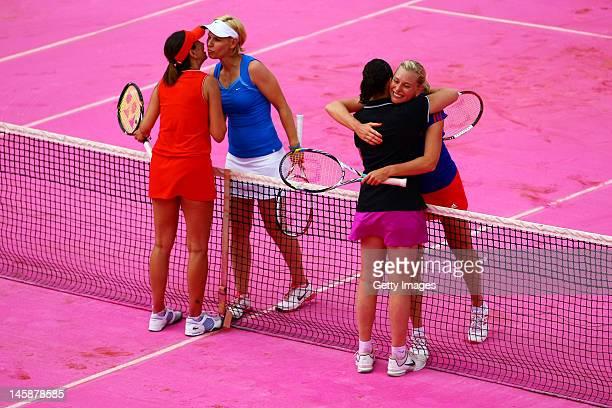 Conchita Martinez of Spain hugs Barbara Schett of Austria at the net as her partner Iva Majoli of Croatia kisses Anke Huber of Germany after their...