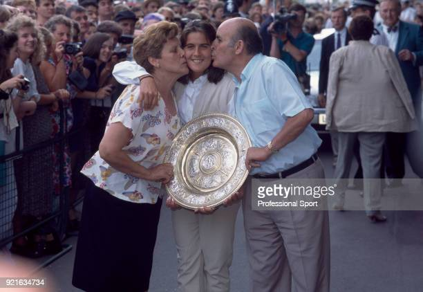 Conchita Martinez of Spain poses with her parents after defeating Martina Navratilova of the USA in the Women's Singles Final of the Wimbledon Lawn...