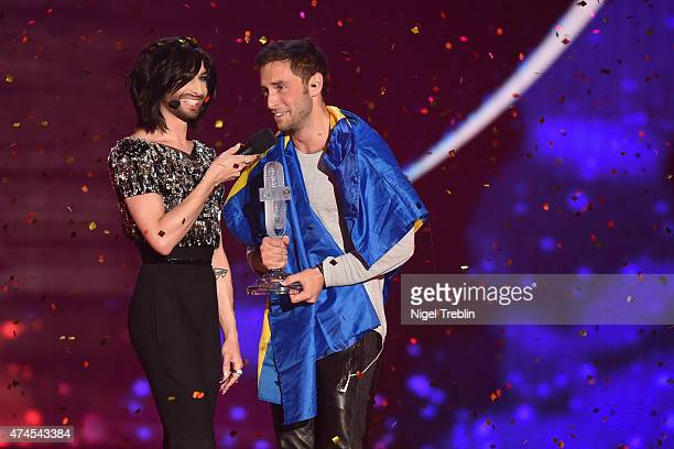 Conchita Wurst hands over the trophy to Mans Zelmerloew of Sweden after winning the final of the Eurovision Song Contest 2015 on May 23 2015 in...